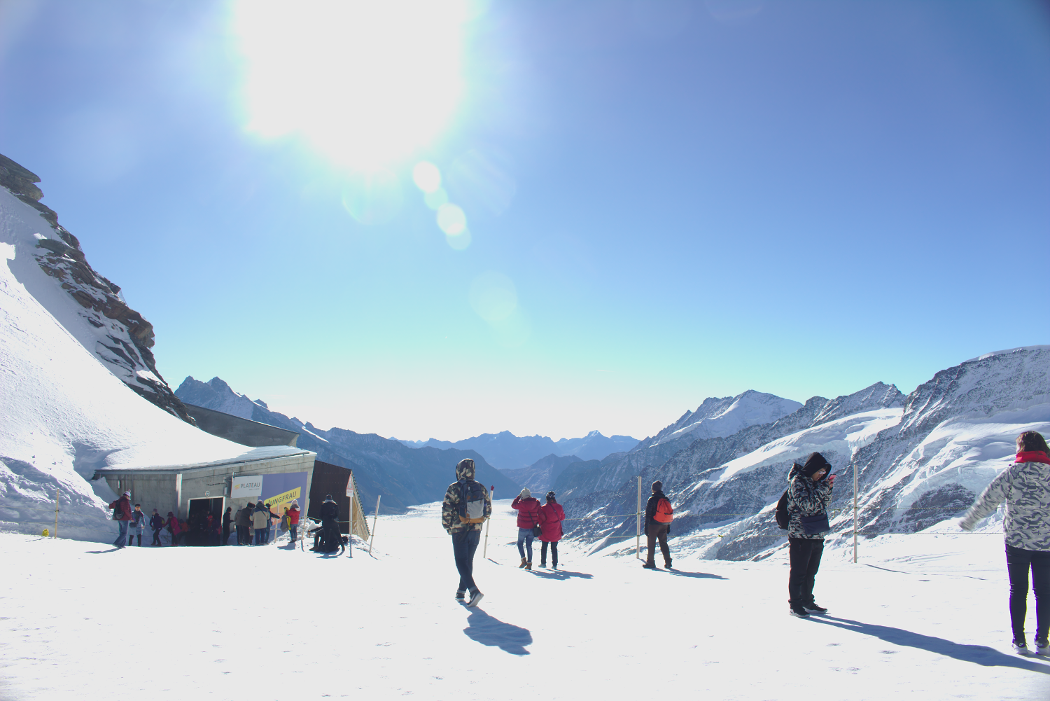 Photo of tourists standing in front of panorama of glacier