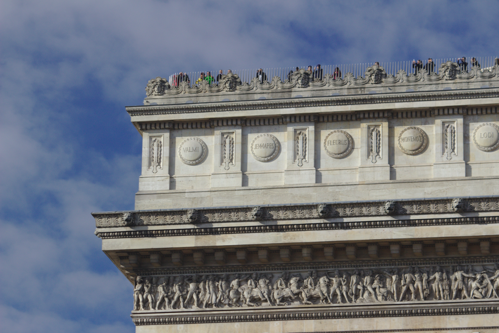 Image of people looking over the railing at the top of the Arc de Triomphe.